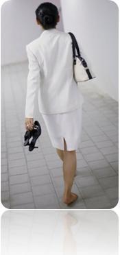 mulher usa vestido tailler anda descalça segura sapatos apertados num corredor de prédio